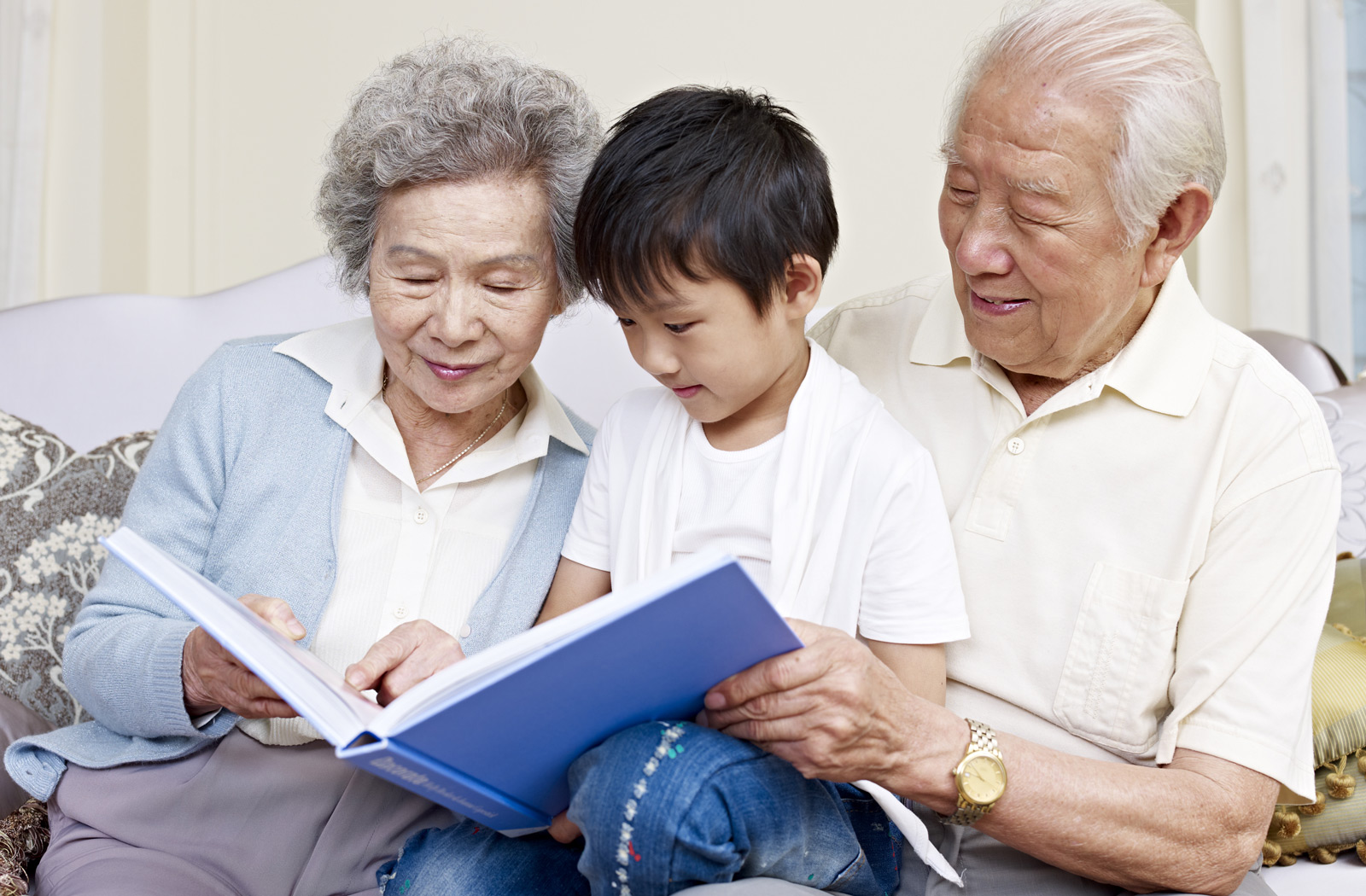 Grandparents and grandson reading book