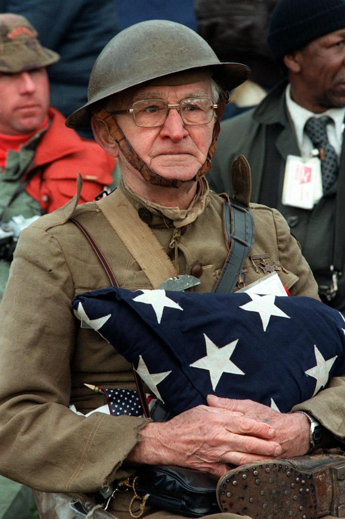World War I veteran holding folded flag