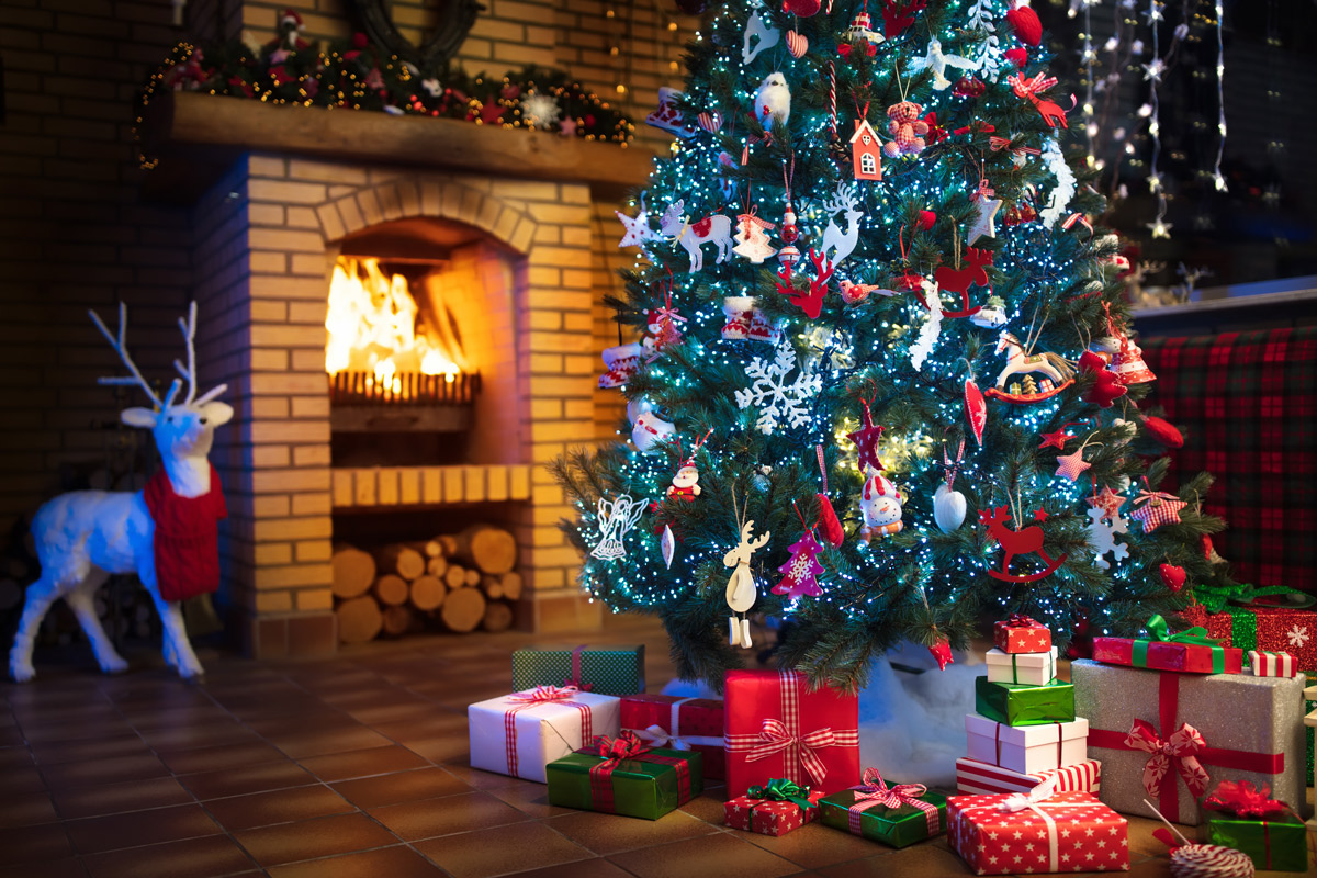 decorated Christmas tree with presents in front of fireplace