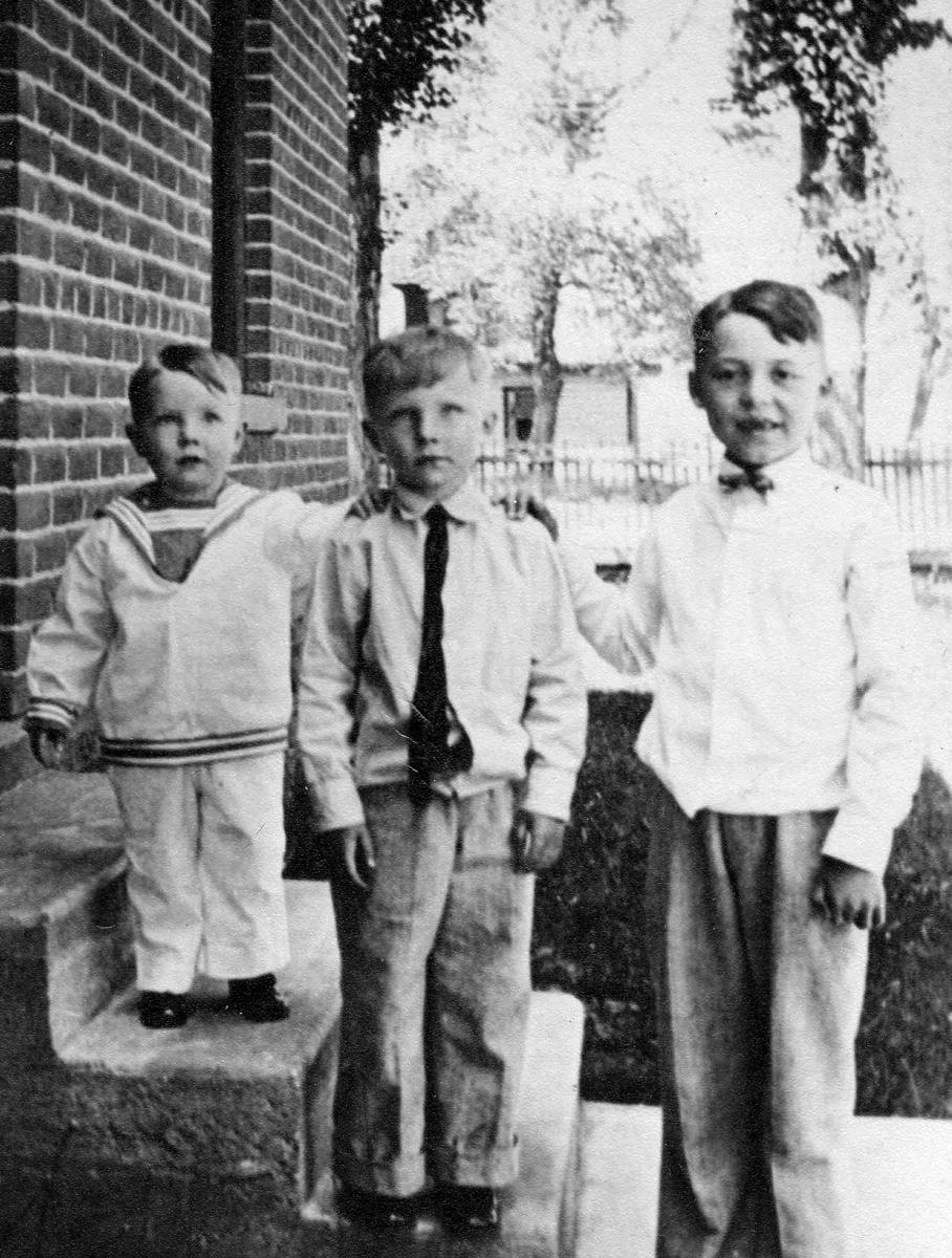 three boys standing on steps